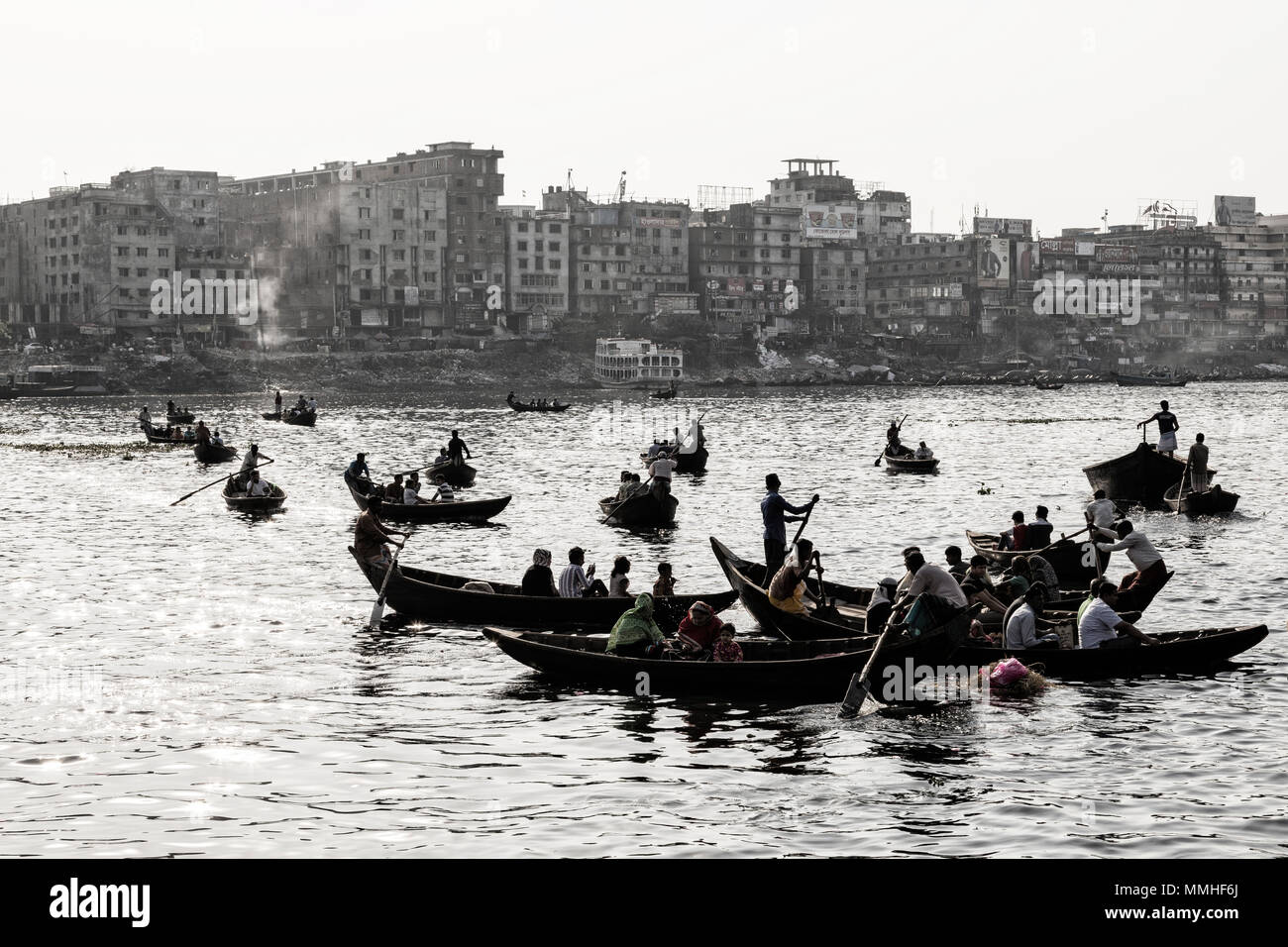 Dhaka, Bangladesh, February 24 2017: Backlit shot of small wooden boats used as a taxi operate on the Buriganga River in Dhaka Bangladesh (Vintage Pho - Stock Image