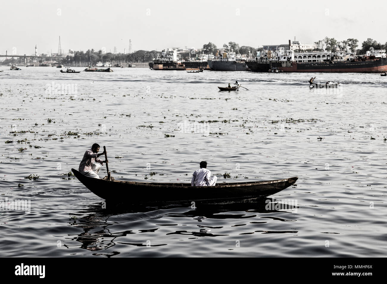 Dhaka, Bangladesh, February 24 2017: Rowing boats on the Buriganga River in Dhaka Bangladesh and in the background the old shipyard (Vintage Photo) - Stock Image