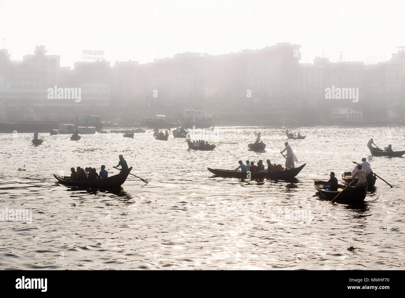 Dhaka, Bangladesh, February 24 2017: Backlit shot of small wooden boats used as a taxi operate on the Buriganga River in Dhaka Bangladesh on a foggy m - Stock Image