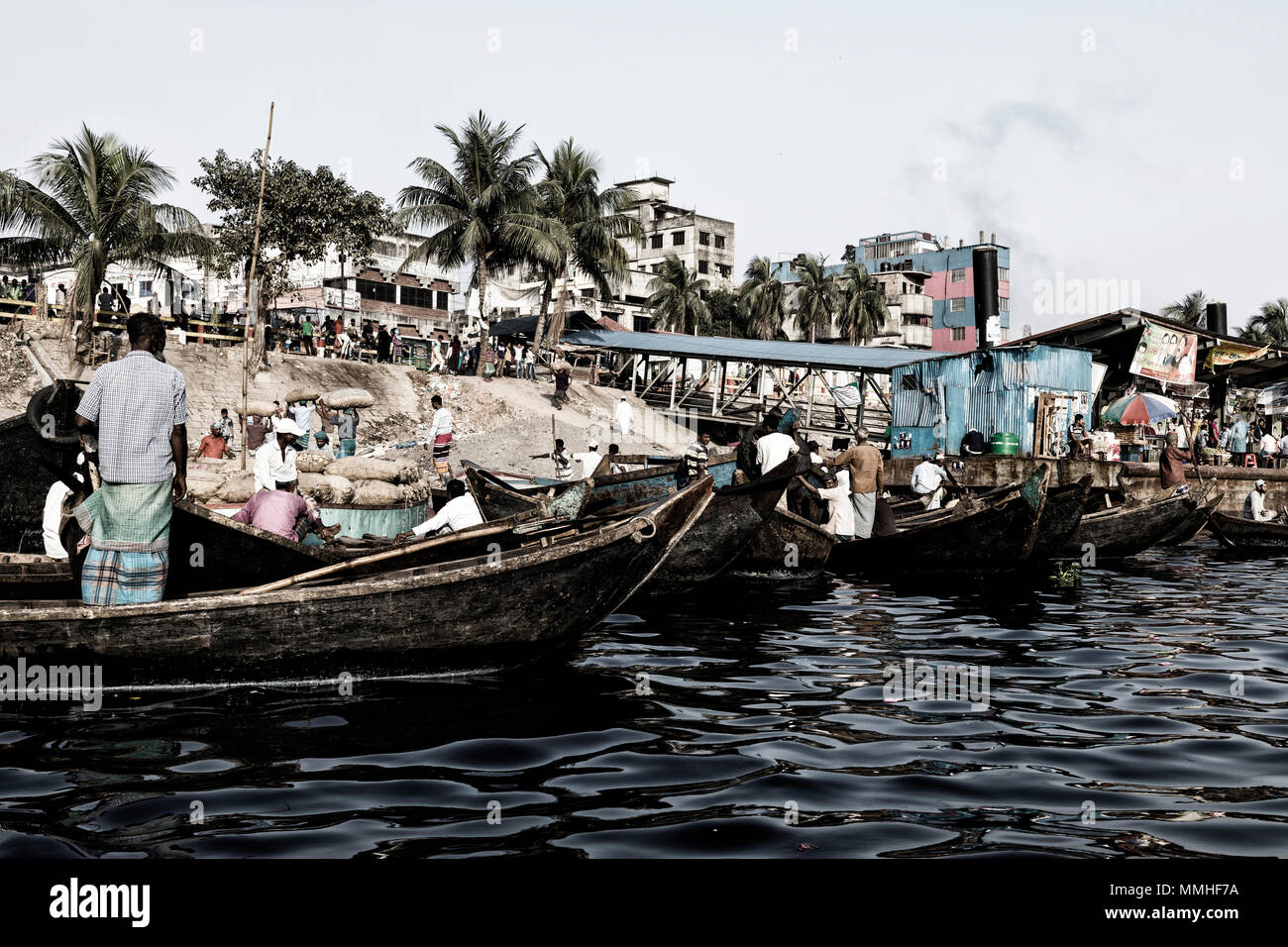 Dhaka, Bangladesh, February 24 2017: Men wait for passengers in their small rowboats at Sadarghat of the Buriganga River in Dhaka Bangladesh (Vintage  - Stock Image