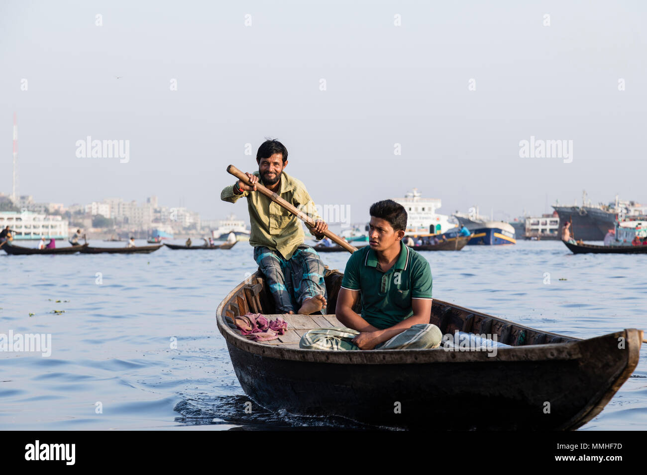 Dhaka, Bangladesh, February 24 2017: Wooden taxi boat with passengers and a cargo ship in background on the Buriganga River in Dhaka Bangladesh - Stock Image