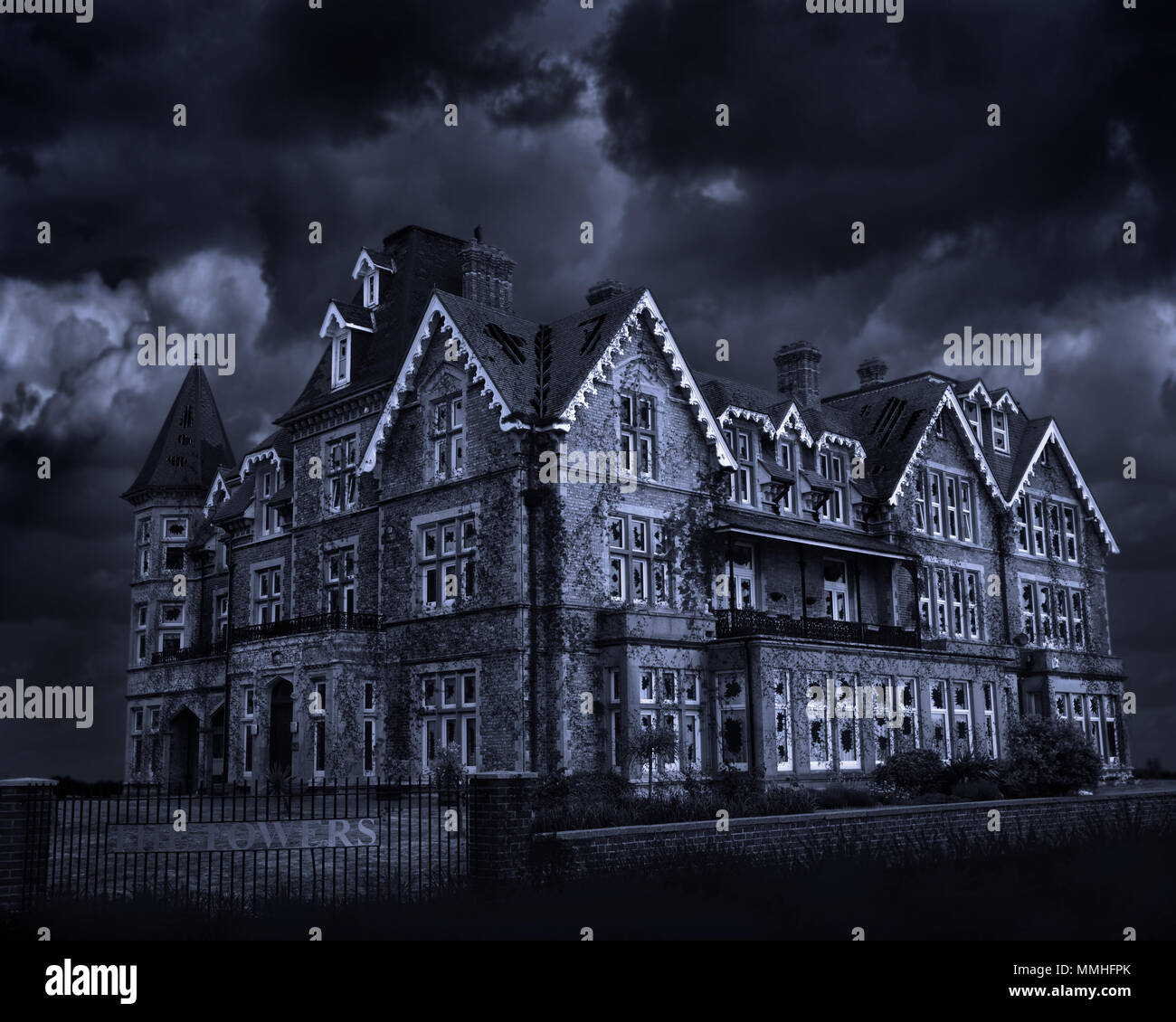 This image is a photo manipulation of a block of apartments that is in good repair and made to look as though it's derelict, run down and haunted. - Stock Image
