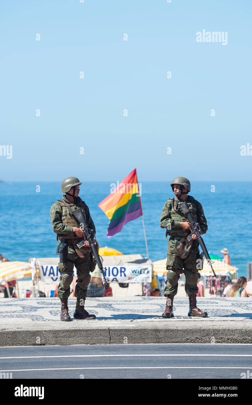 RIO DE JANEIRO - FEBRUARY 10, 2017: Two Brazilian Army soldiers stand in full camouflage uniform on the boardwalk at Ipanema Beach to provide security - Stock Image