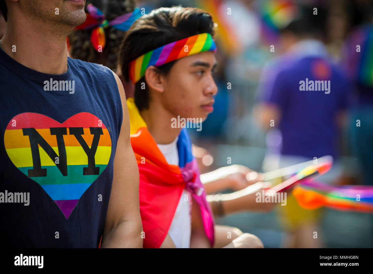 NEW YORK CITY - JUNE 25, 2017: Supporters wave rainbows flags and wear heart NY t-shirt on the sidelines of the Pride Parade in Greenwich Village. - Stock Image