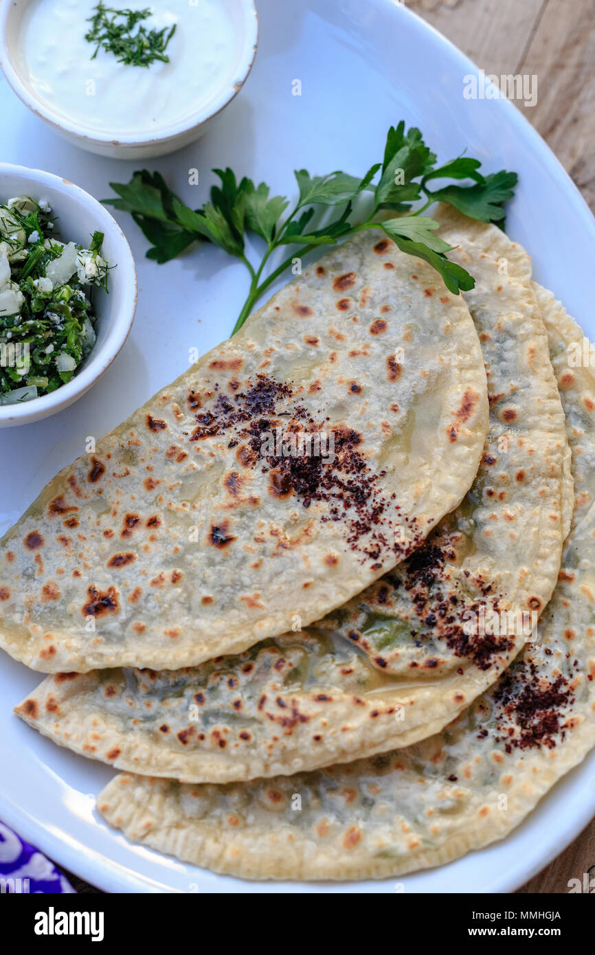 traditional Azerbaijani cuisine. Upper view shot of qutabs flatbread with greens. - Stock Image