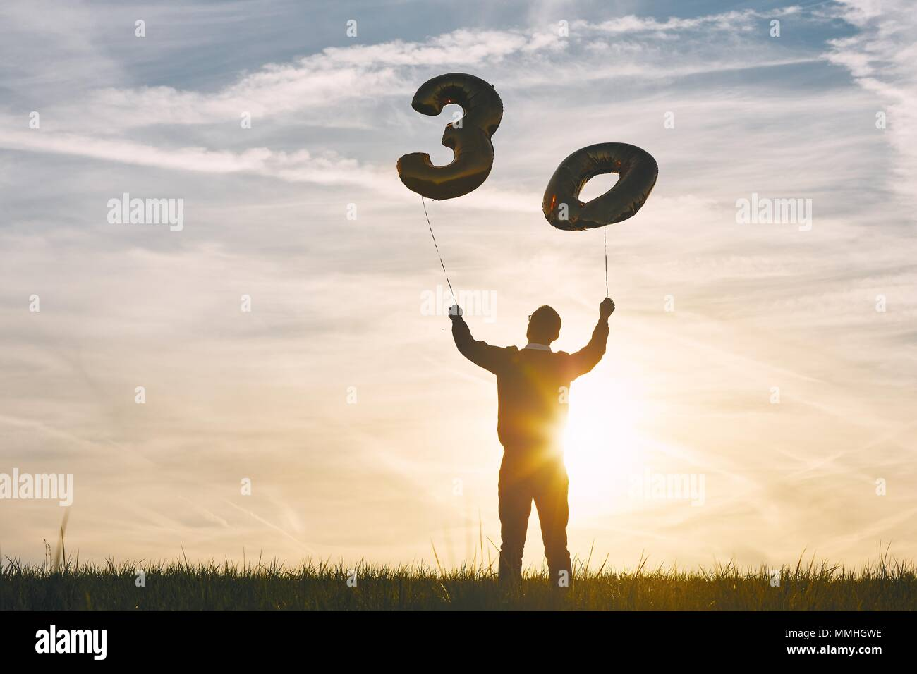 Man celebrates thirty years birthday. Person holding helium balloons in shape of number 30 at sunset. Stock Photo
