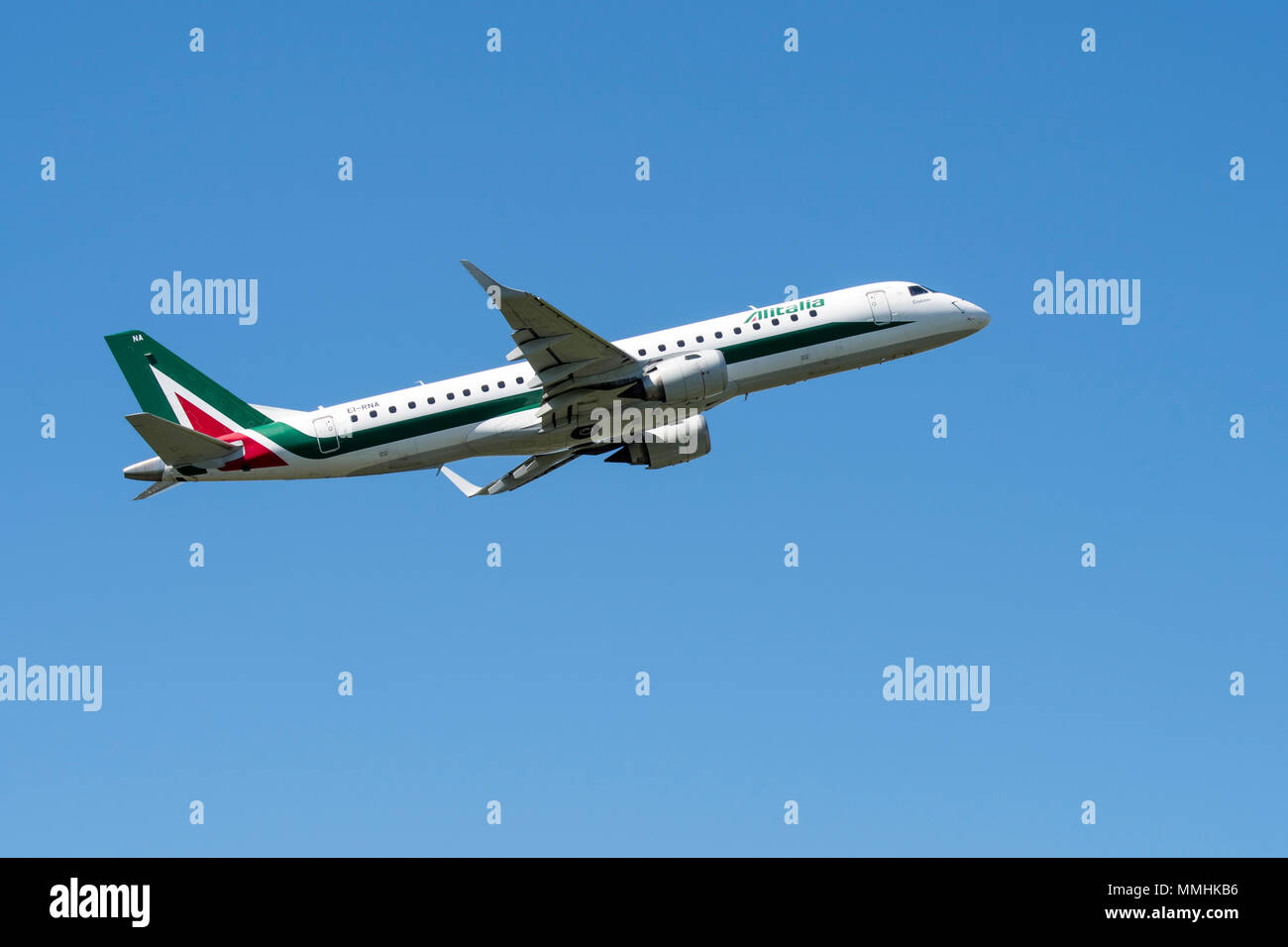 Embraer ERJ-190-100LR, narrow-body medium-range twin-engine jet airliner from Alitalia CityLiner, Italian airline in flight against blue sky - Stock Image
