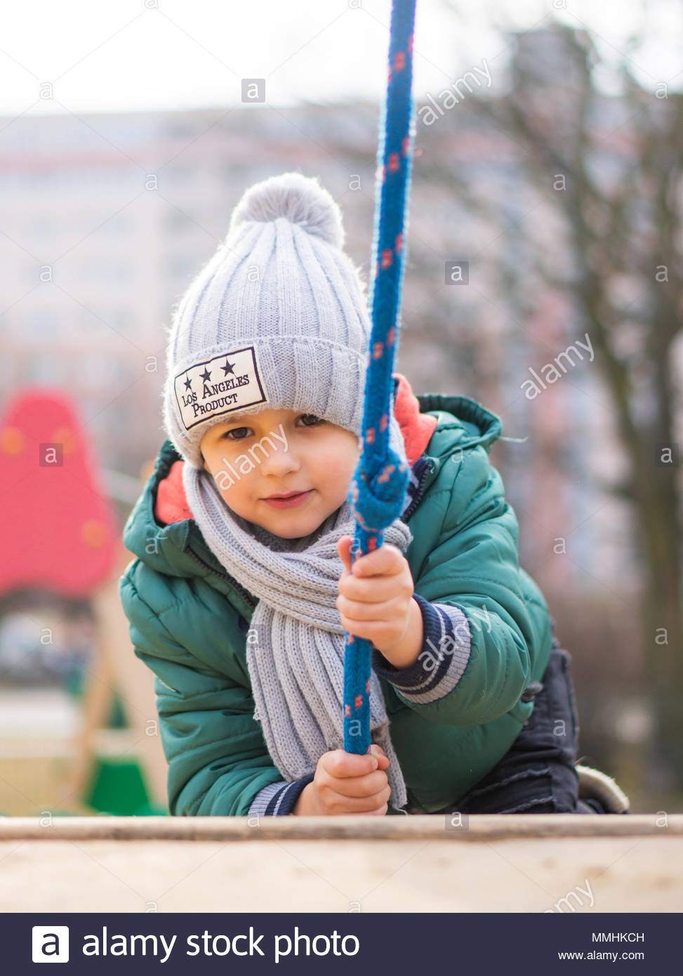 Young boy with warm hat climbing on a equipment at a playground in Poznan, Poland - Stock Image