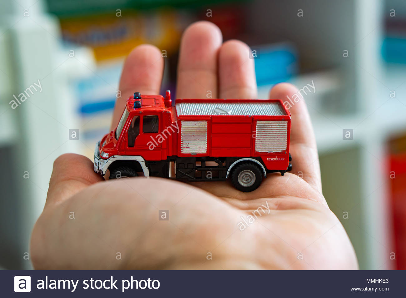 Red Siku model toy fire truck on a open hand - Stock Image