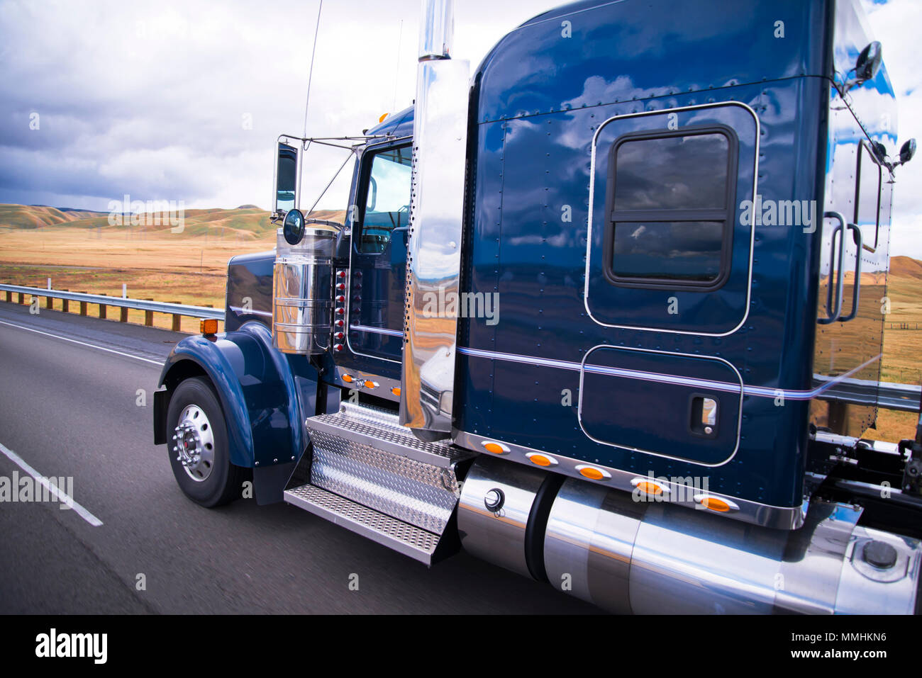 Dark blue shiny classic American big rig semi truck with chrome accessories with reflection on cab surface running on the road with yellow summer fiel - Stock Image