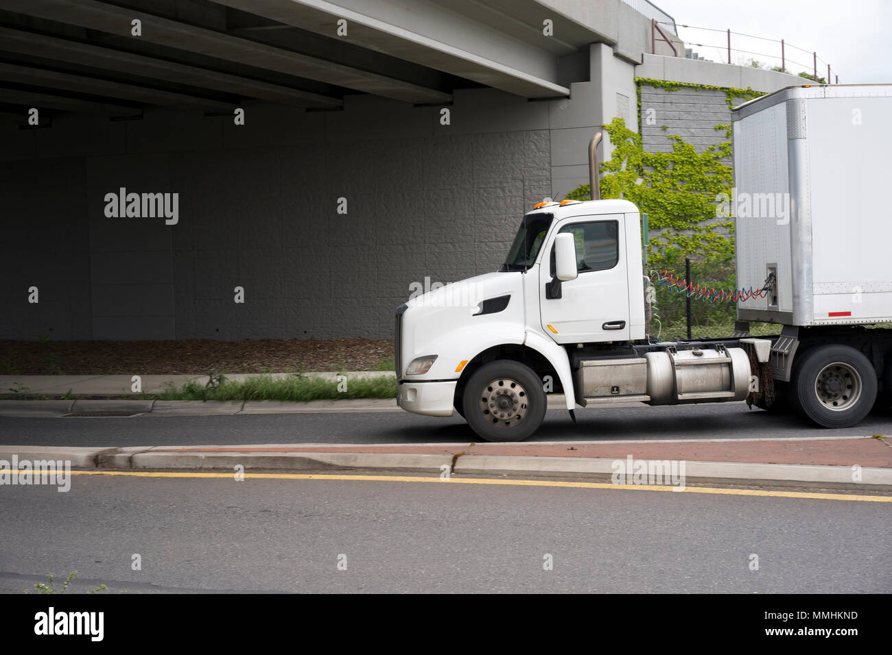 Profile of day cab big rig white semi truck for local transportation