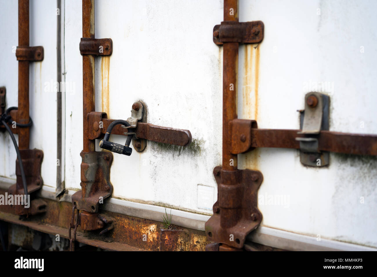 Old rusted door closing mechanism of the semi trailer which fulfilled its technical resource and became useless with digital lock for robbery prevent  - Stock Image