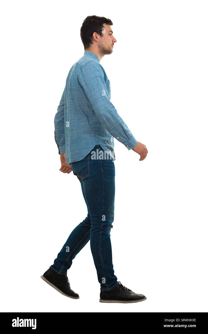 Full length profile shot of a young confident man walking isolated on white background - Stock Image