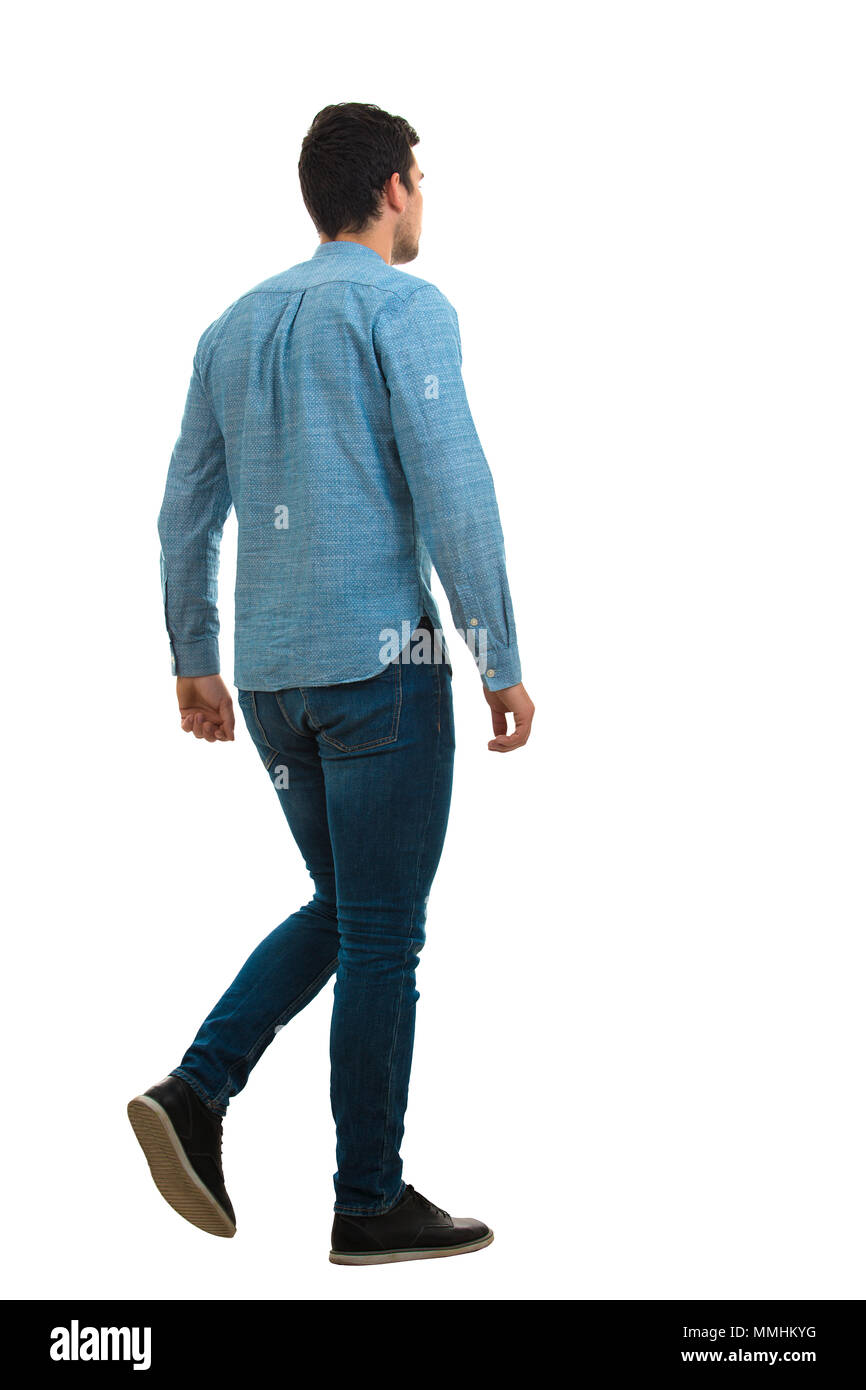 Full length back portrait of a young man walking isolated on white background. - Stock Image