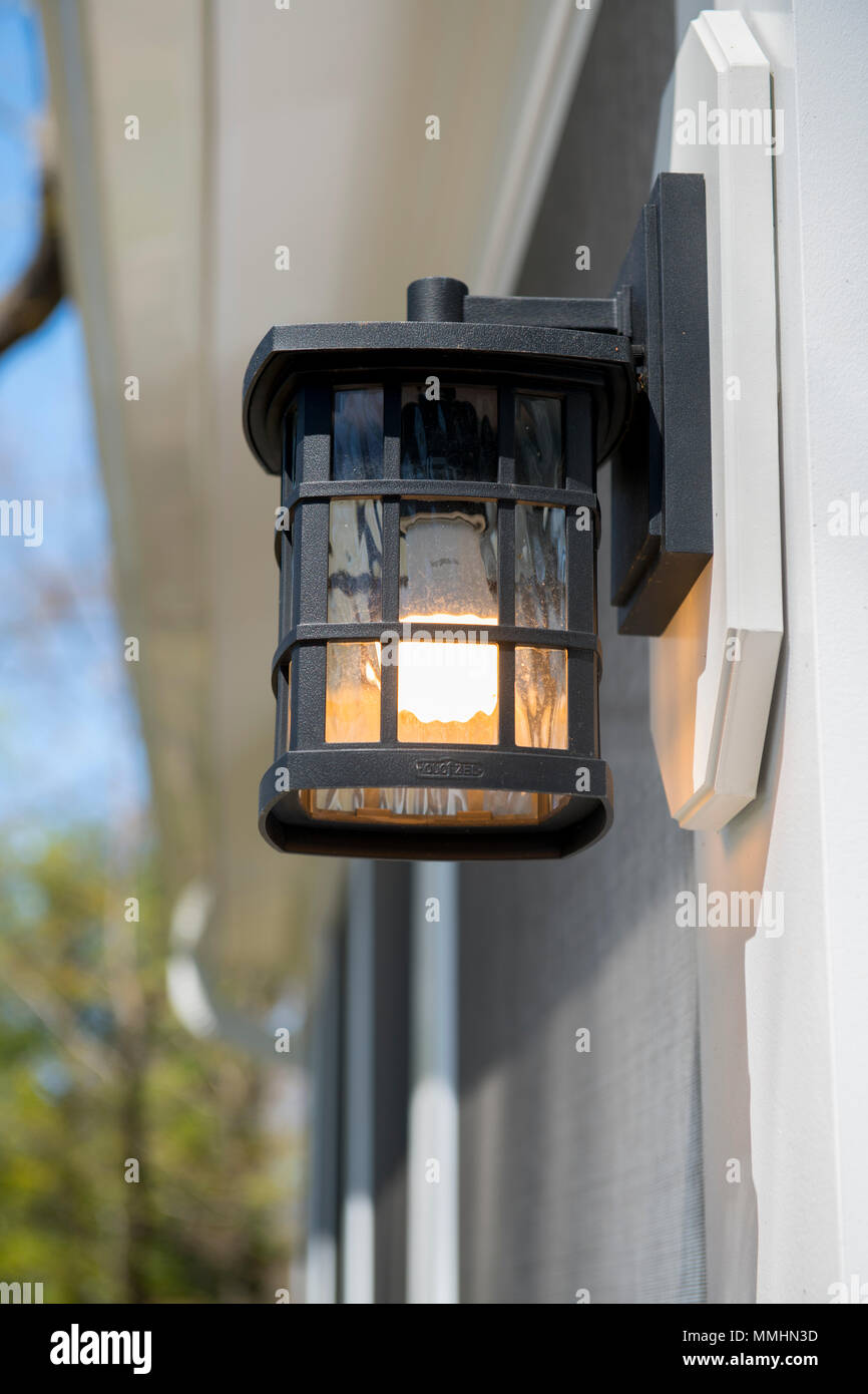 An Outdoor Wall Light Sconce With A Low Energy Bulb Lighting A House Door Stock Photo Alamy