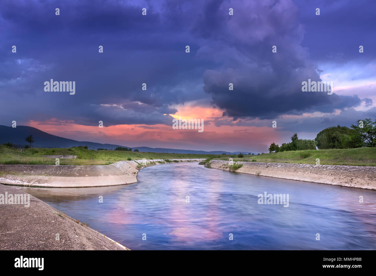 Amazing, dramatic sunset colors and fluffy clouds over reflective, curvy river blue hour composition - Stock Image