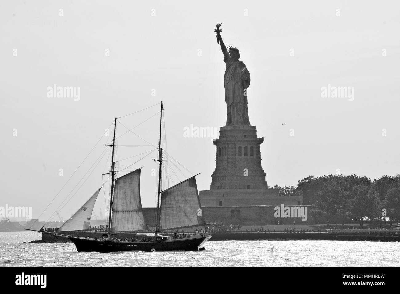 An old sailboat sails in front of the Statue of Liberty at the entrance of New York Harbor, New York, USA - Stock Image