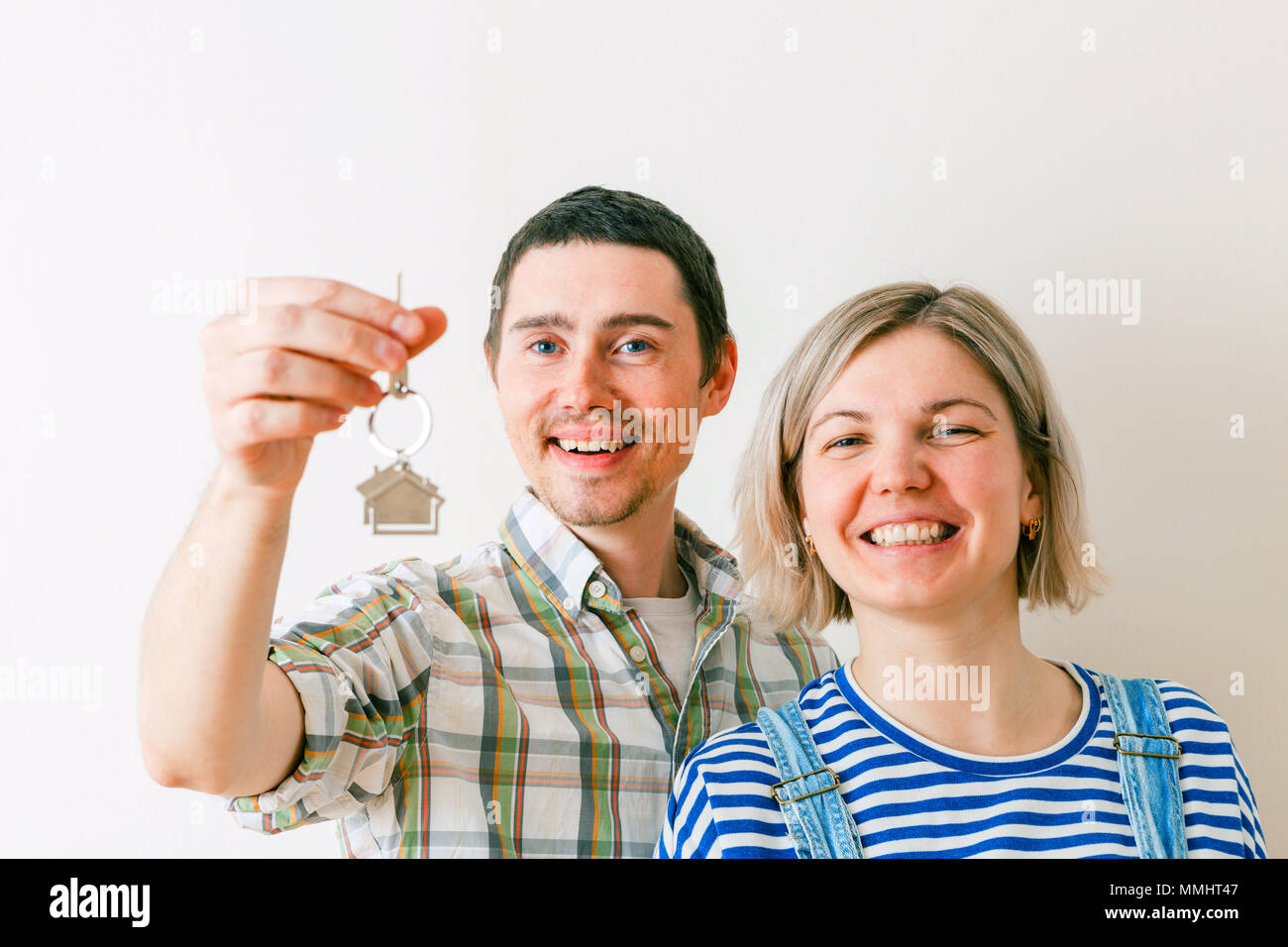 Photo of woman and man with keys from apartment against blank wall - Stock Image