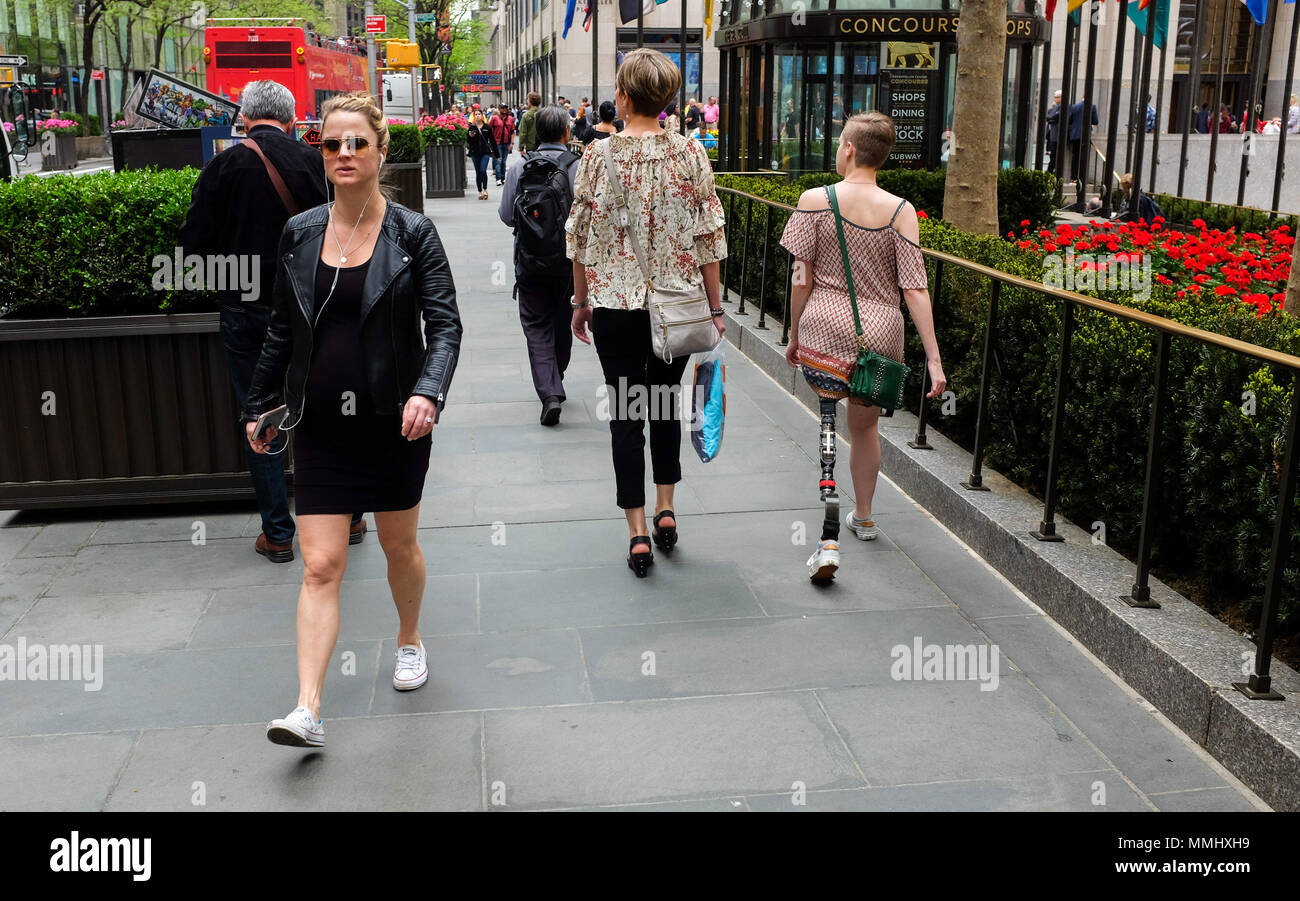 a young woman with a prosthetic leg walks on a sidewalk in New York City May 10, 2018. - Stock Image