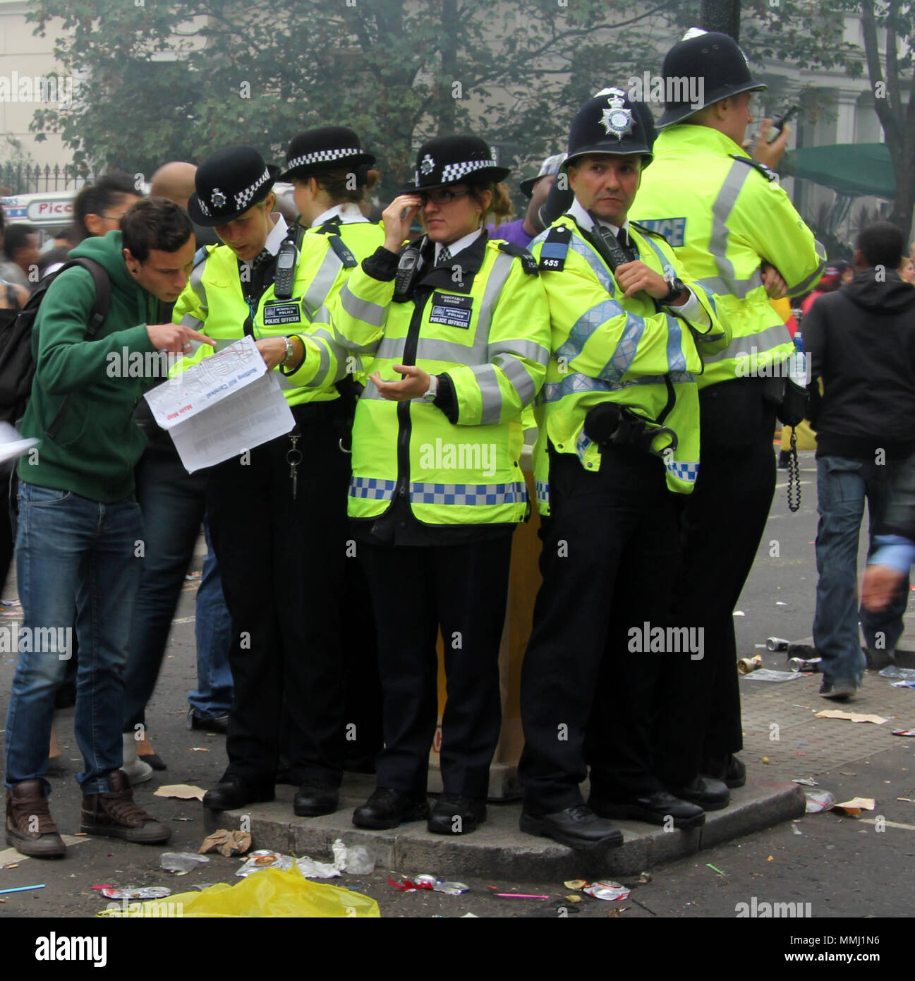 A bunch of coppers standing on a traffic island during Notting hill carnival.  The police stick together in the mayhem - Stock Image