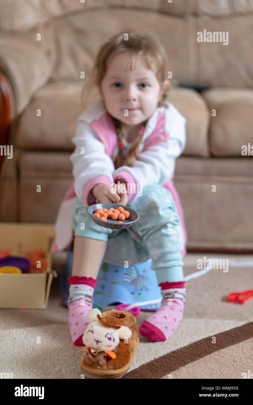 Little four years old girl sitting on potty and play with kinetic sand, toys and slippers scattered around. Carefree childhood - Stock Image
