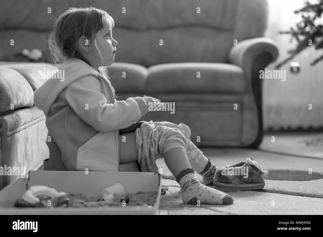 Little four years old girl sitting on potty, playing with kinetic sand and watching TV, monochrome effect - Stock Image