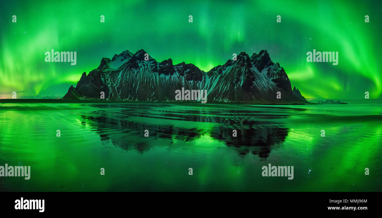 Aurora reflections on Stokksnes black beach with Vestrahorn mountains in center, Iceland Stock Photo