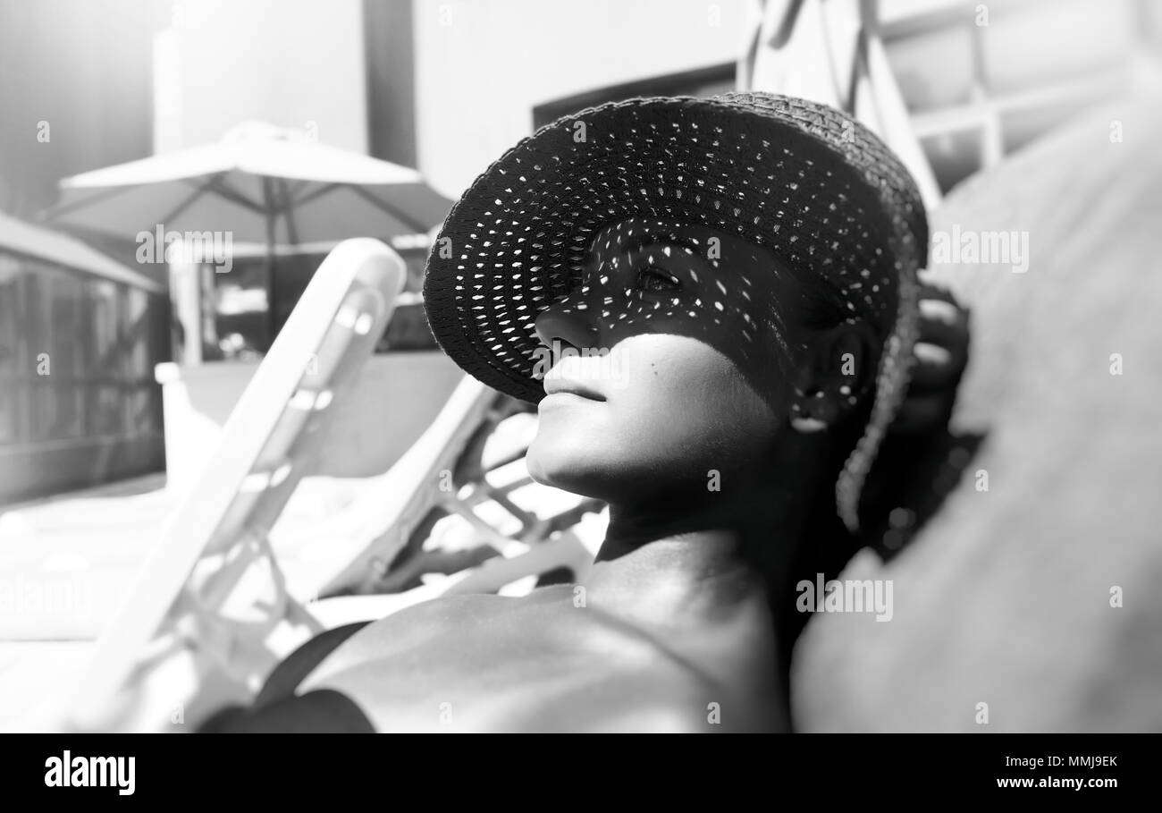 Black and white photo of a pretty woman lying down on a sunbed on the beach resort wearing stylish big hat to protect the face from sunlight