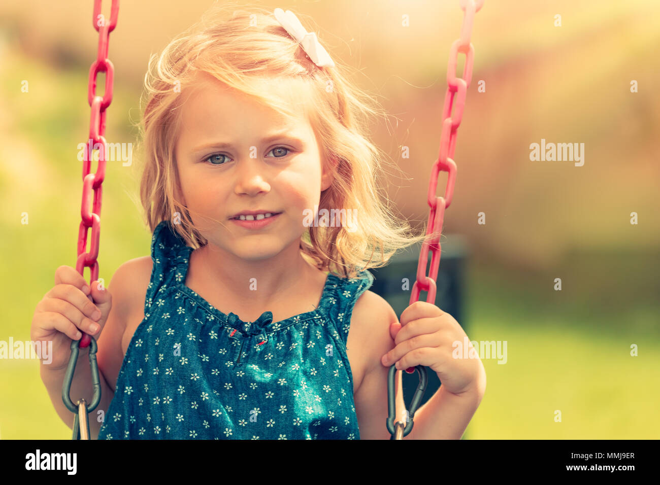 cute baby girl swinging on swing outdoors, nice adorable child