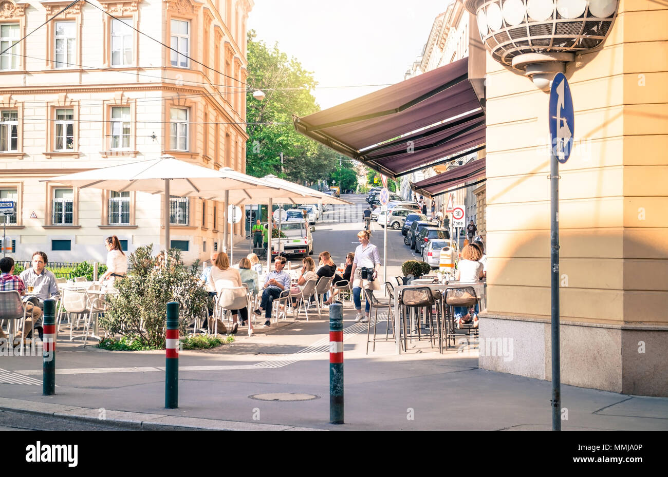 Vienna Austria May 3. 2018, European street coffeehouse, people sitting outside enjoying sunny weather - Stock Image