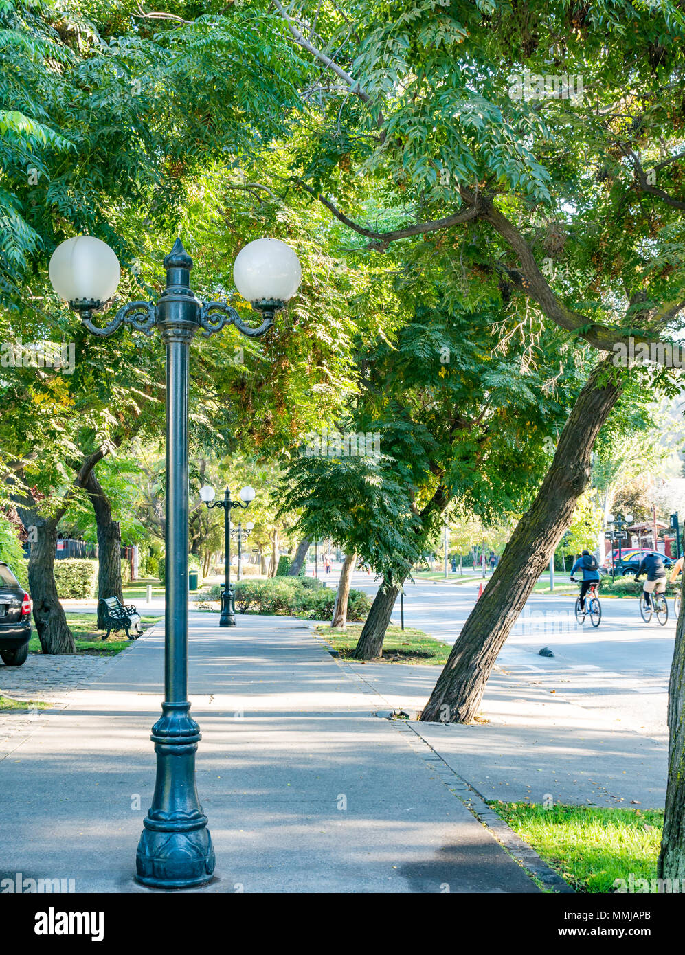 Pedro de Valdivia Street, quiet on Easter Sunday and closed to cars for public recreation with cyclists and old fashioned lamp post - Stock Image