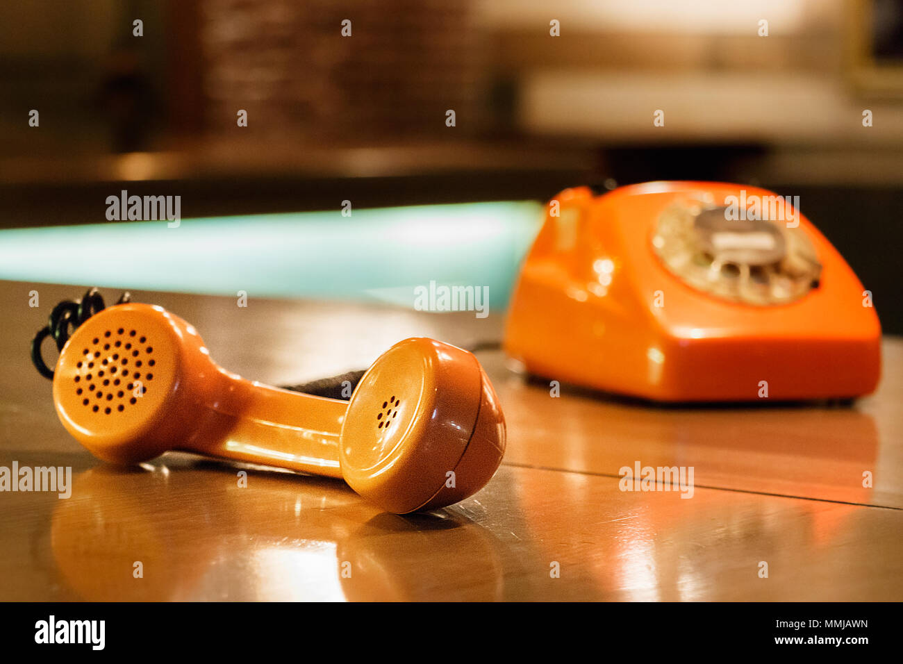 Handset of an orange telephone with dial placed on a wooden table inside a bar. - Stock Image