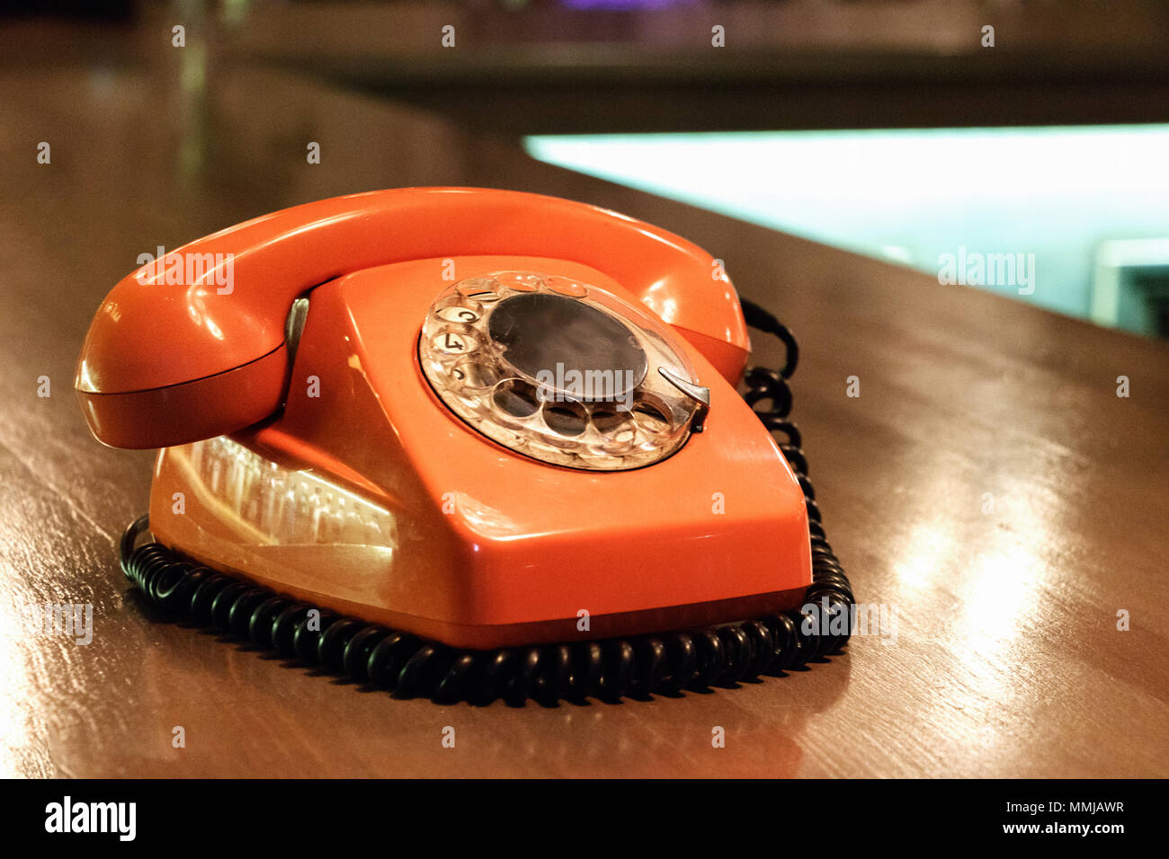 A vintage plastic orange telephone with dial placed on a wooden table inside a bar. - Stock Image
