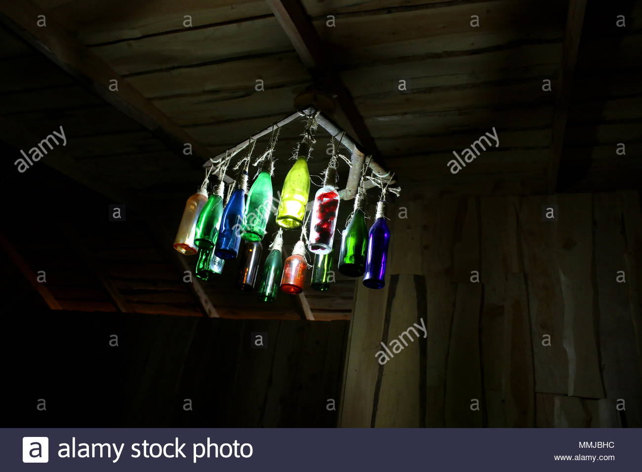 colorful glass bottles as light fixtures - Stock Image