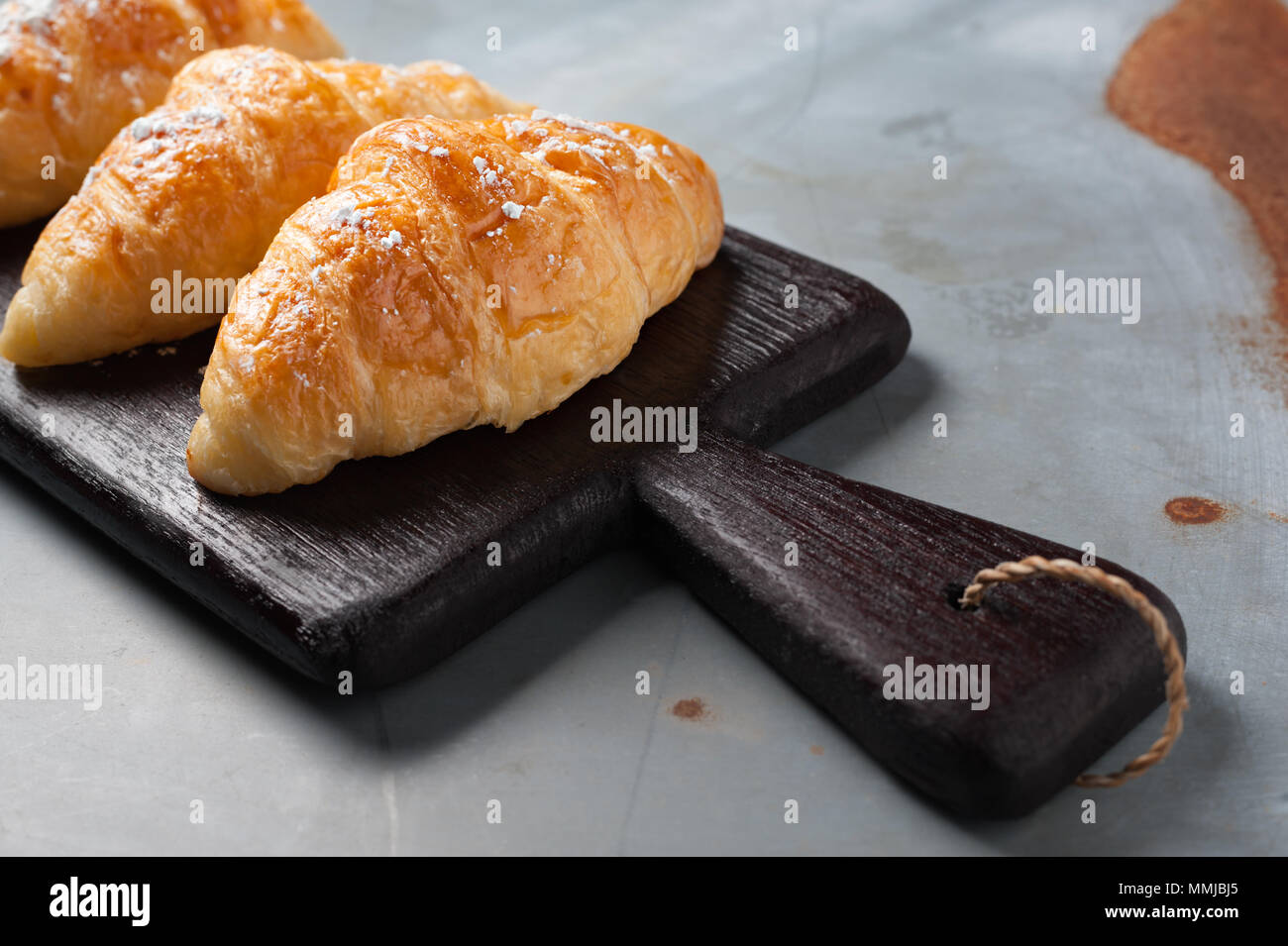 Fresh baked croissant sprinkled with powdered sugar on table - Stock Image