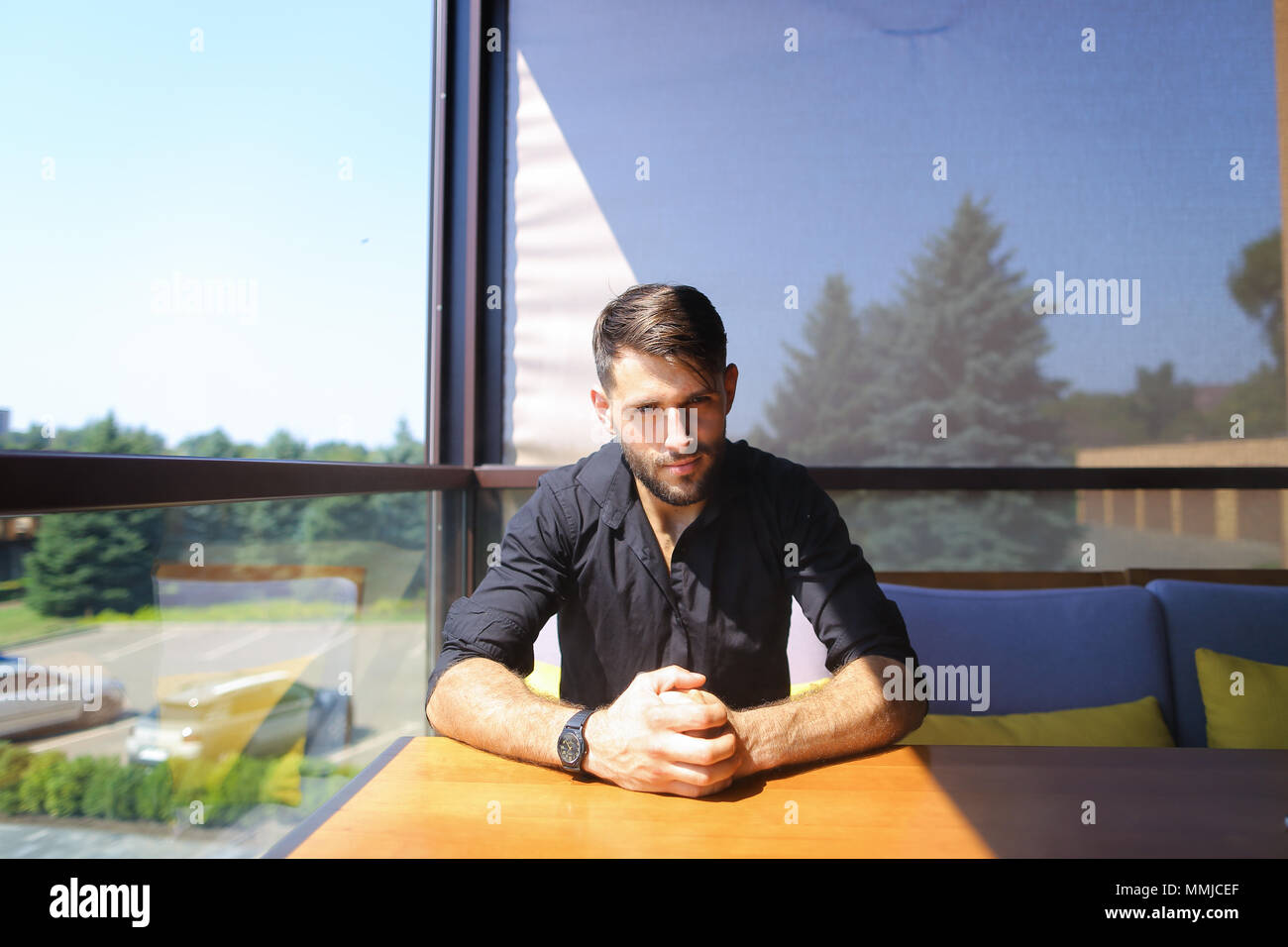 European male manager sitting at office on sofa and wearing black shirt. - Stock Image