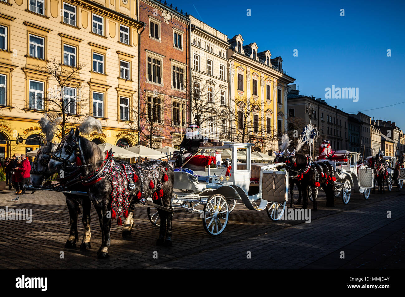 KRAKOW, POLAND - DECEMBER 16, 2016. Horse carriages at main square in Krakow in a sunny day, Poland - Stock Image