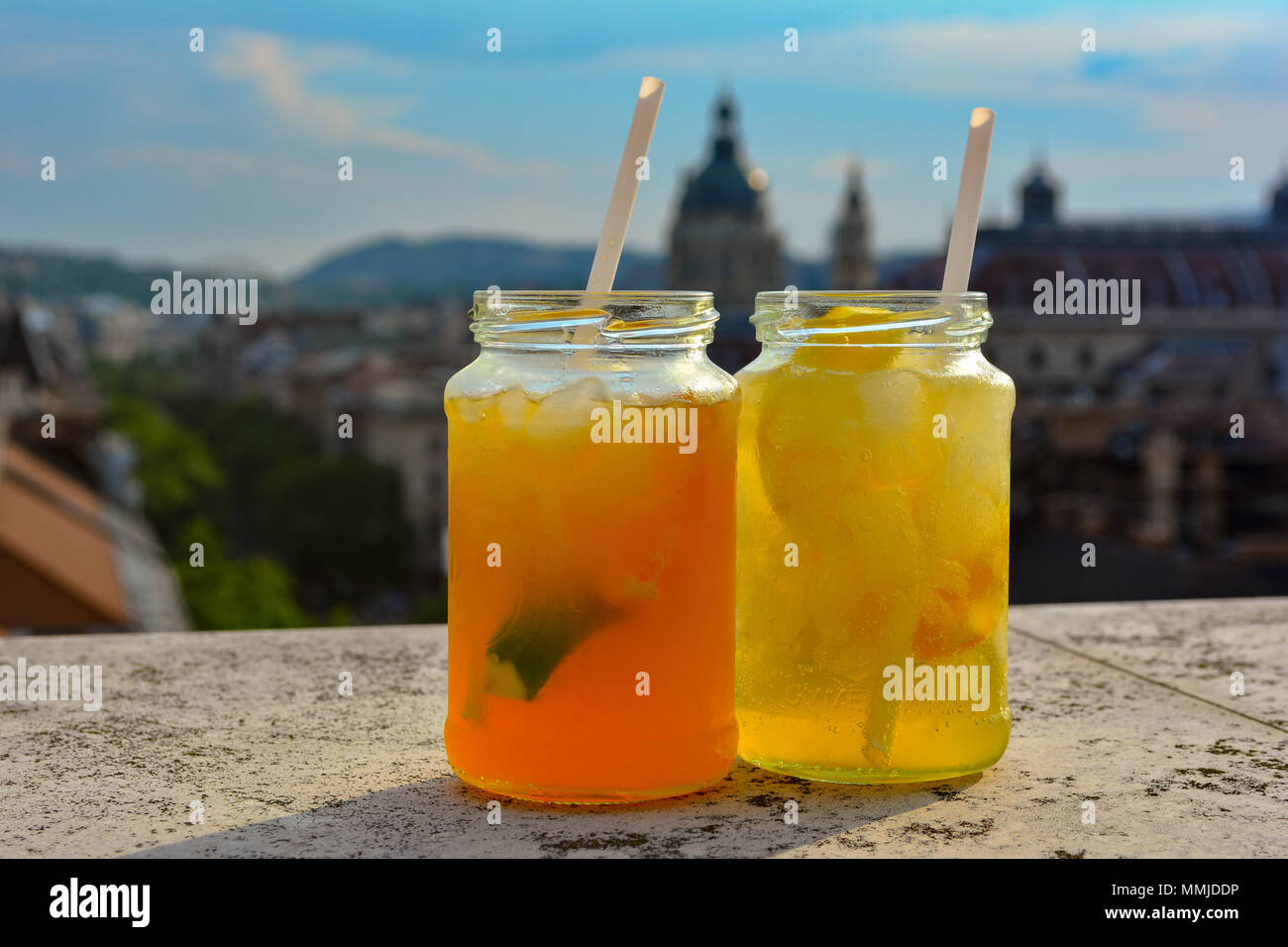 Cocktail glasses with refreshing lemonade on table in rooftop bar against city view. Beautiful rooftop bar in Budapest, Hungary. - Stock Image