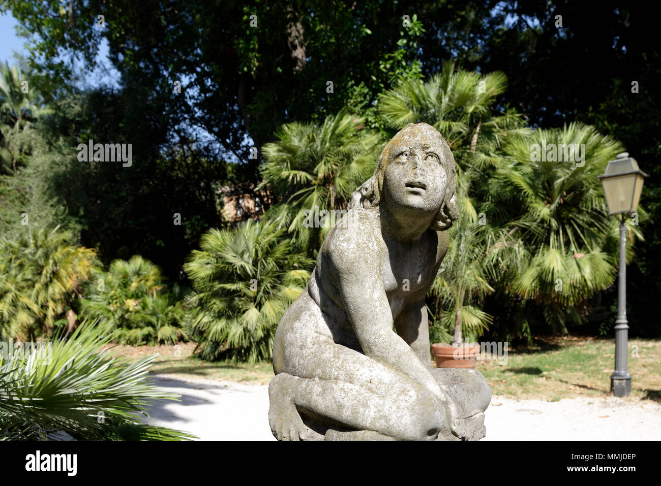 Post classic marble statue of couching Boy at the Orto Botanico di Roma or Rome's Botanical Garden. Located on the lower slopes of Gianicolo or Janicu - Stock Image