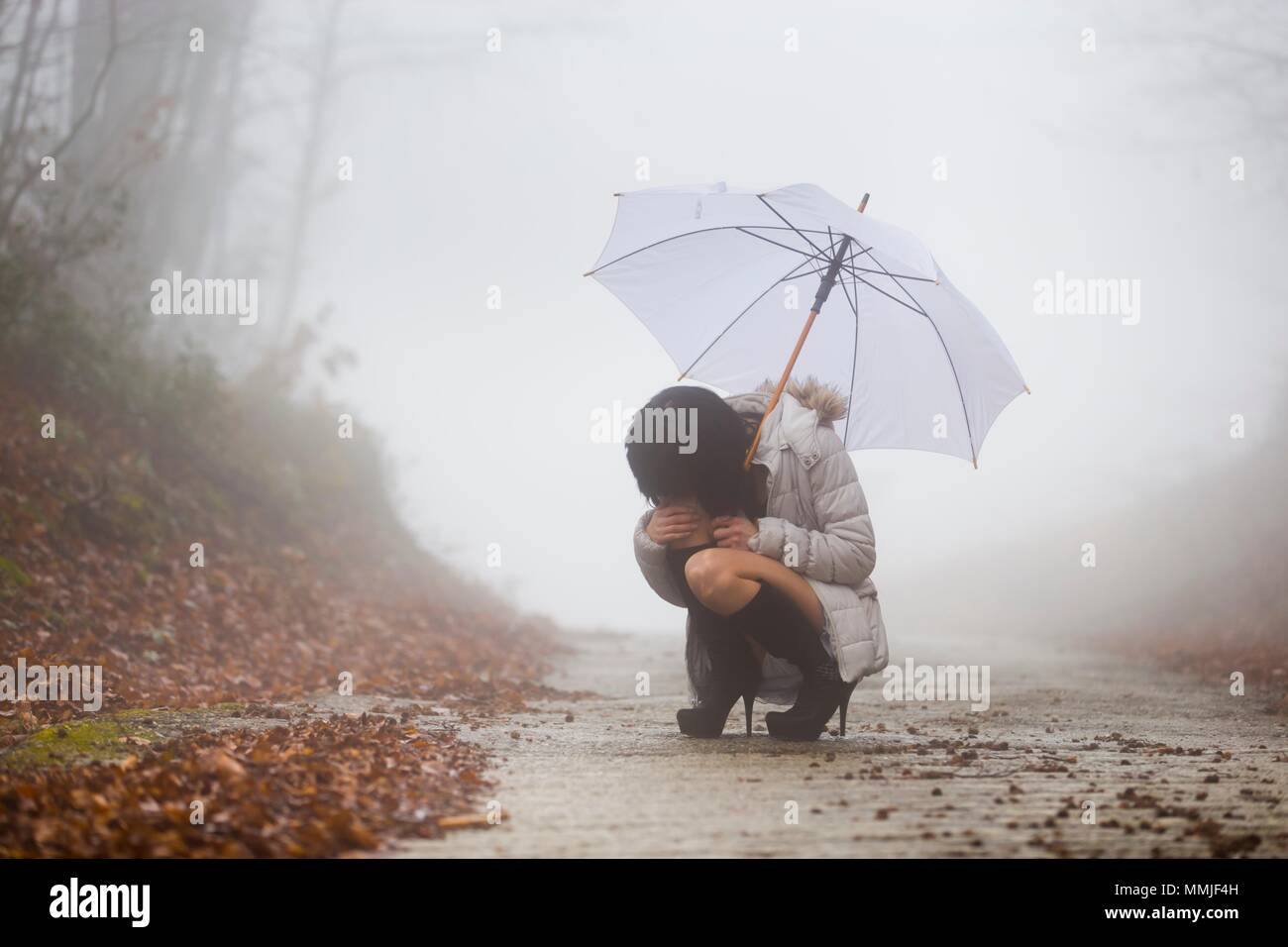 Young 20s woman desperate hiding eyes lost in fog umbrella in hand limited visibility on country road - Stock Image