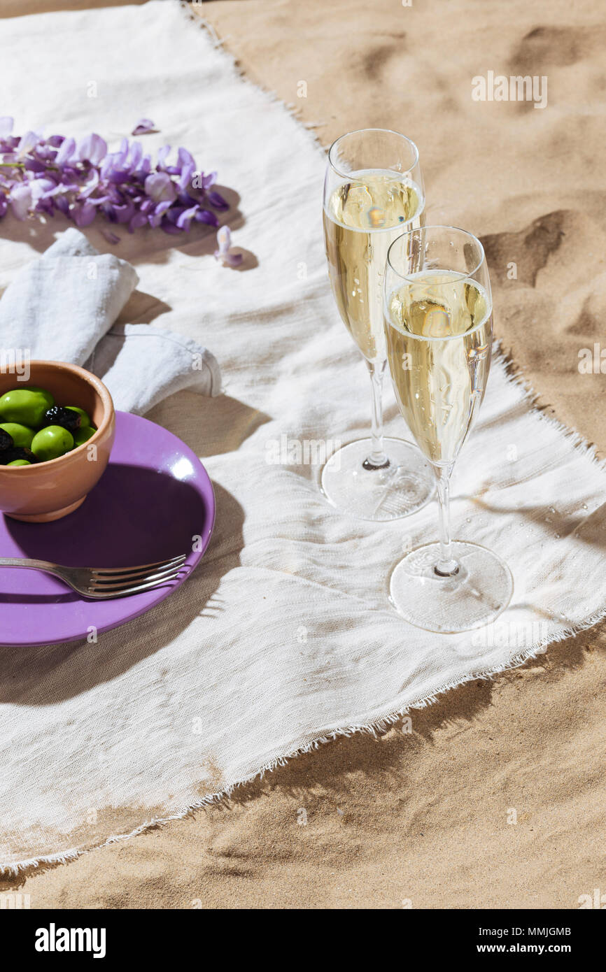 Picnic on the beach with prosecco calix and olives - Stock Image