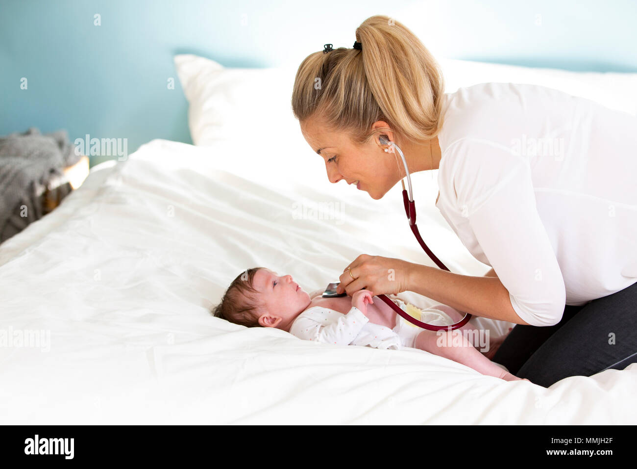Pediatrician examines baby with stethoscope at home - Stock Image