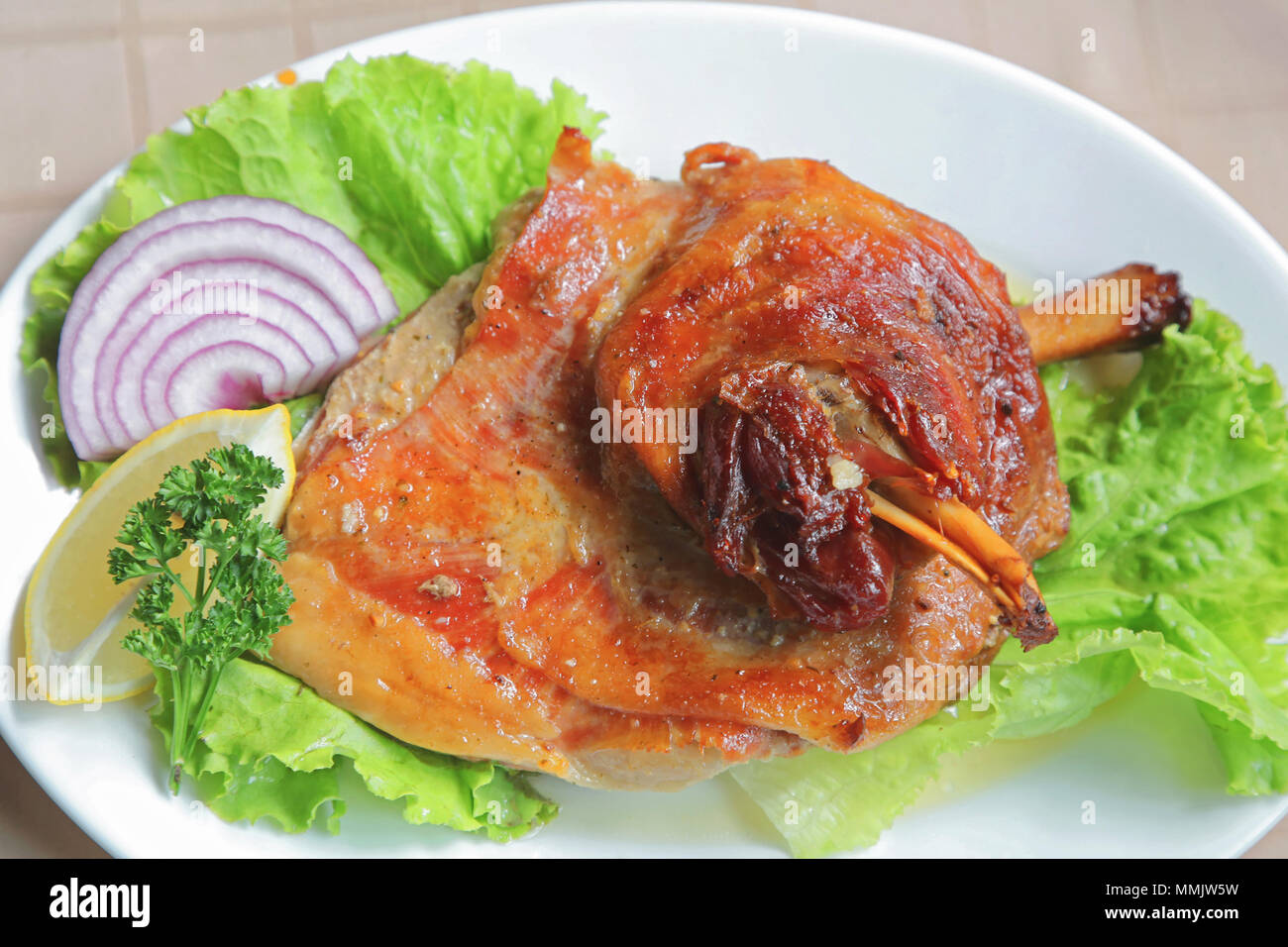 Roasted Lamb Shank Served With Salad and Onion - Stock Image