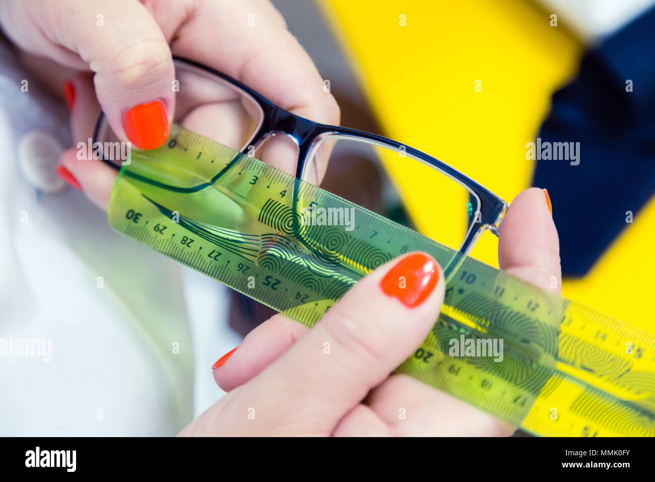 The doctor ophthalmologist determines the distance between the optical centers of the lenses in glasses with flexible ruler tool. Glasses in female ha - Stock Image