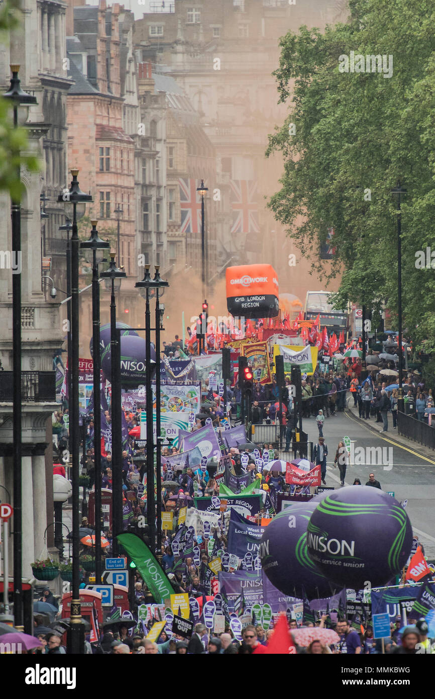 London, UK. 12th May 2018. London, UK. 12th March 2018. Smoke from the GMB union fills the street as the march moves down Piccadilly as the rain comes down - TUC deal for working people -- march, demo & rally. Starting on the Embankment and ending with speeches in Hyde Park. They are marching for a growing economy; For a £10ph minimum wage; For better and free public services; And against racism, sexism and discrimination. Credit: Guy Bell/Alamy Live News Credit: Guy Bell/Alamy Live News - Stock Image