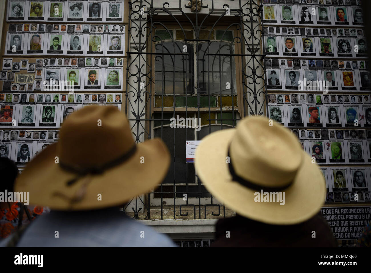 Ciudad De Guatemala, Guatemala. 12th May, 2018. Two men observe the photographs od those disappeared during the civil war (1960-1996), in the Casa de la Memoria, in Guatemala City, Guatemala, on 10 May 2018. In the front yard of the Casa de la Memoria, in the historic center of Guatemala City, some 70 Ixil indigenous people settle in chairs, standing and on the floor to be photographed by personnel from the Center for Legal Action in Human Rights ( CALDH). Credit: EDWIN BERCIÁN/EFE/Alamy Live News - Stock Image