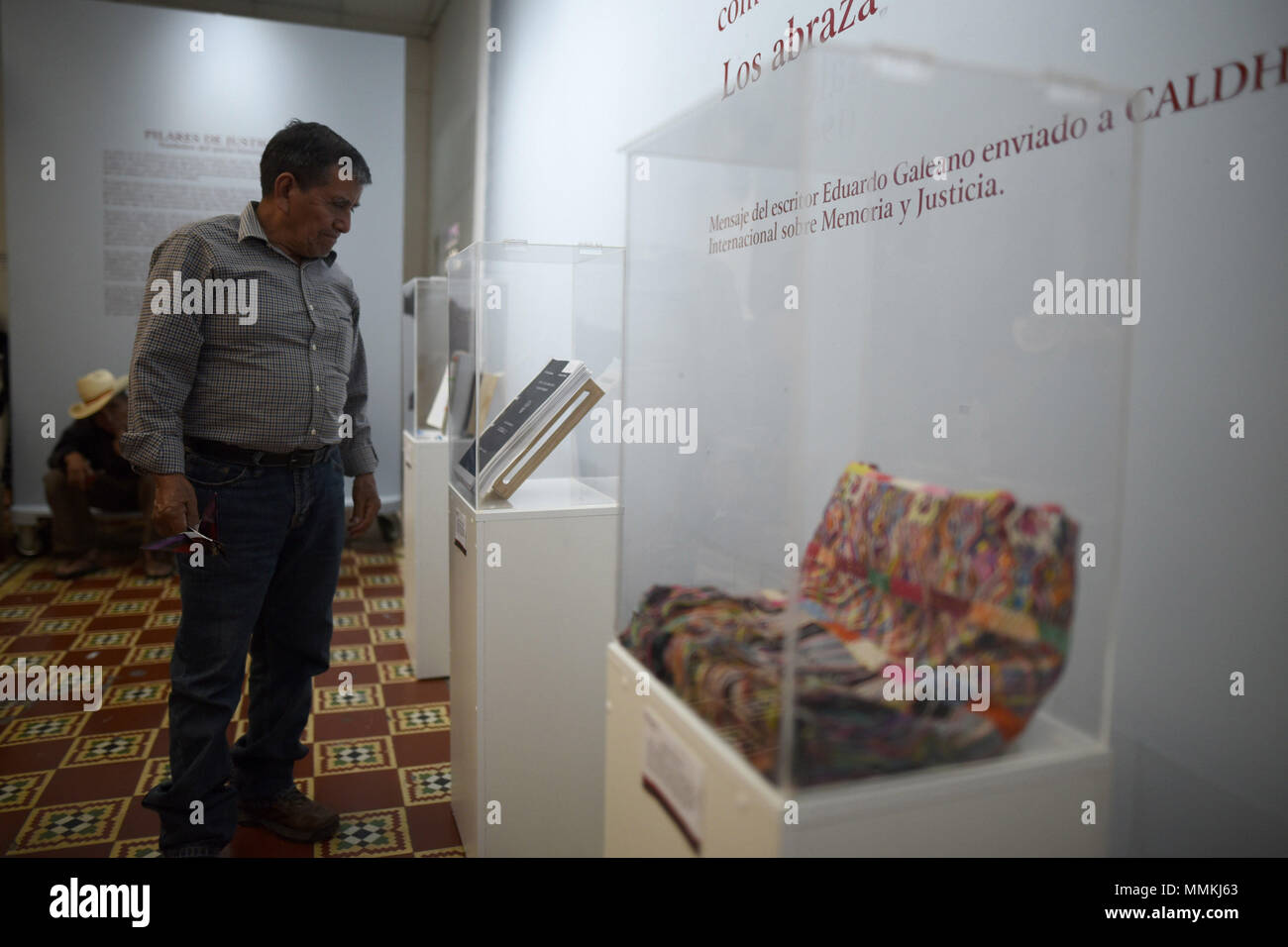 Ciudad De Guatemala, Guatemala. 12th May, 2018. A man observes a certified copy of the Victoria Plan, one of the military strategies used during the civil war (1960-1996), in the Casa de la Memoria, in Guatemala City, Guatemala, on 10 May 2018. In the front yard of the Casa de la Memoria, in the historic center of Guatemala City, some 70 Ixil indigenous people settle in chairs, standing and on the floor to be photographed by personnel from the Center for Legal Action in Human Rights ( CALDH). Credit: EDWIN BERCIÁN/EFE/Alamy Live News - Stock Image