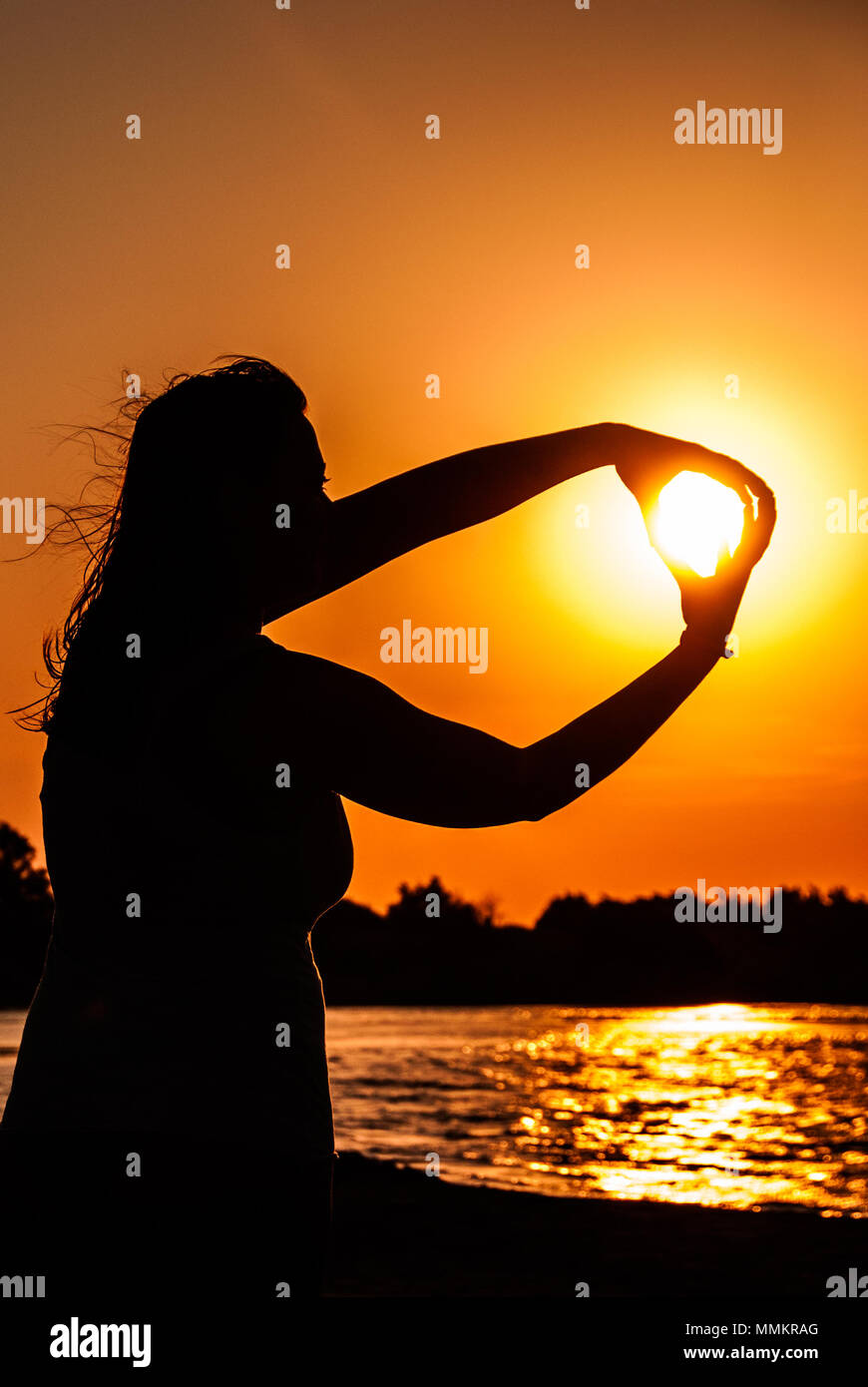 A girl is capturing the sun with her hands in Elafonisi beach in Crete Greece - Stock Image