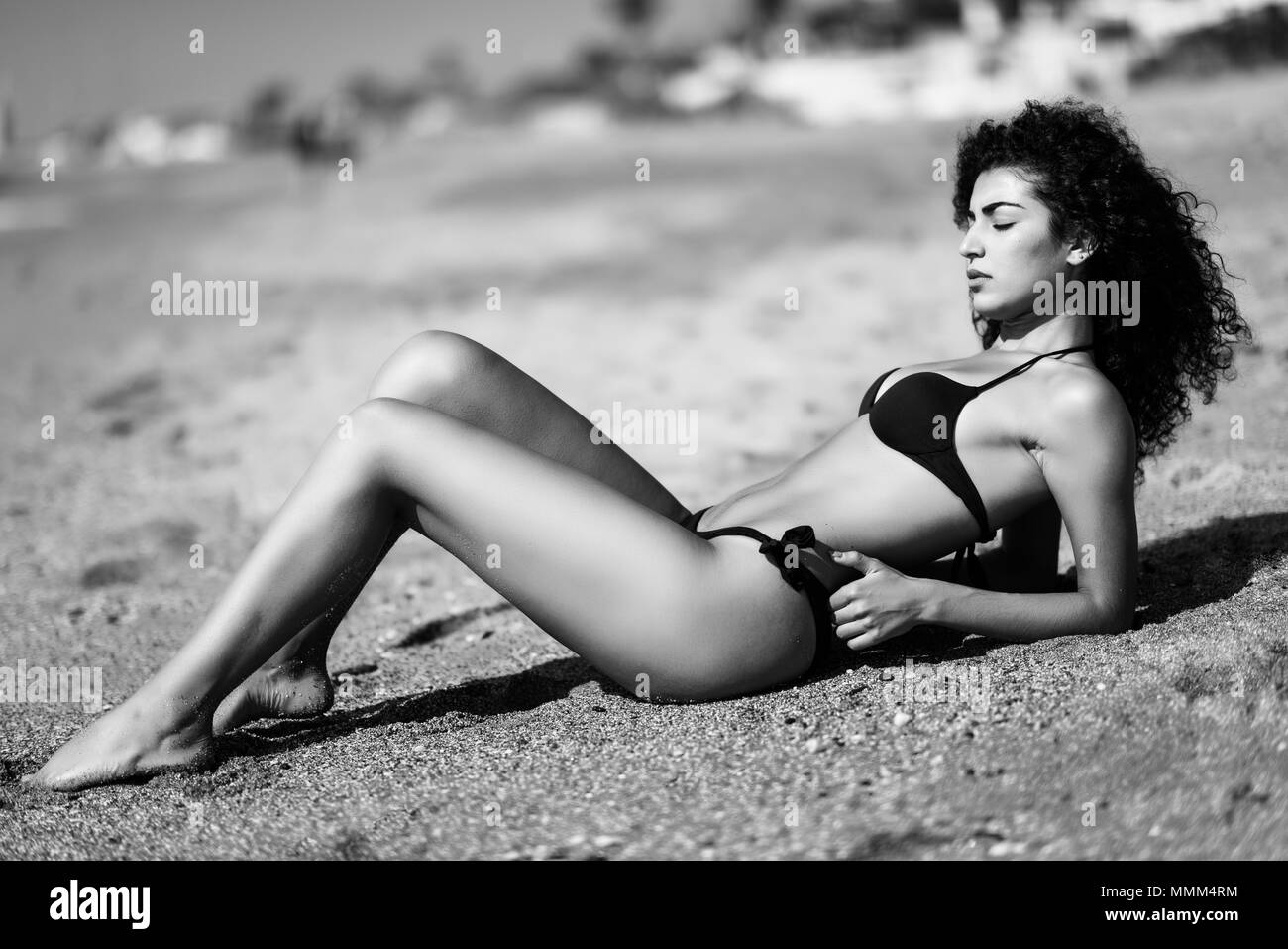 Young arabic woman with beautiful body in swimwear lying on the beach sand. Brunette female with curly long hairstyle wearing black bikini with eyes c - Stock Image
