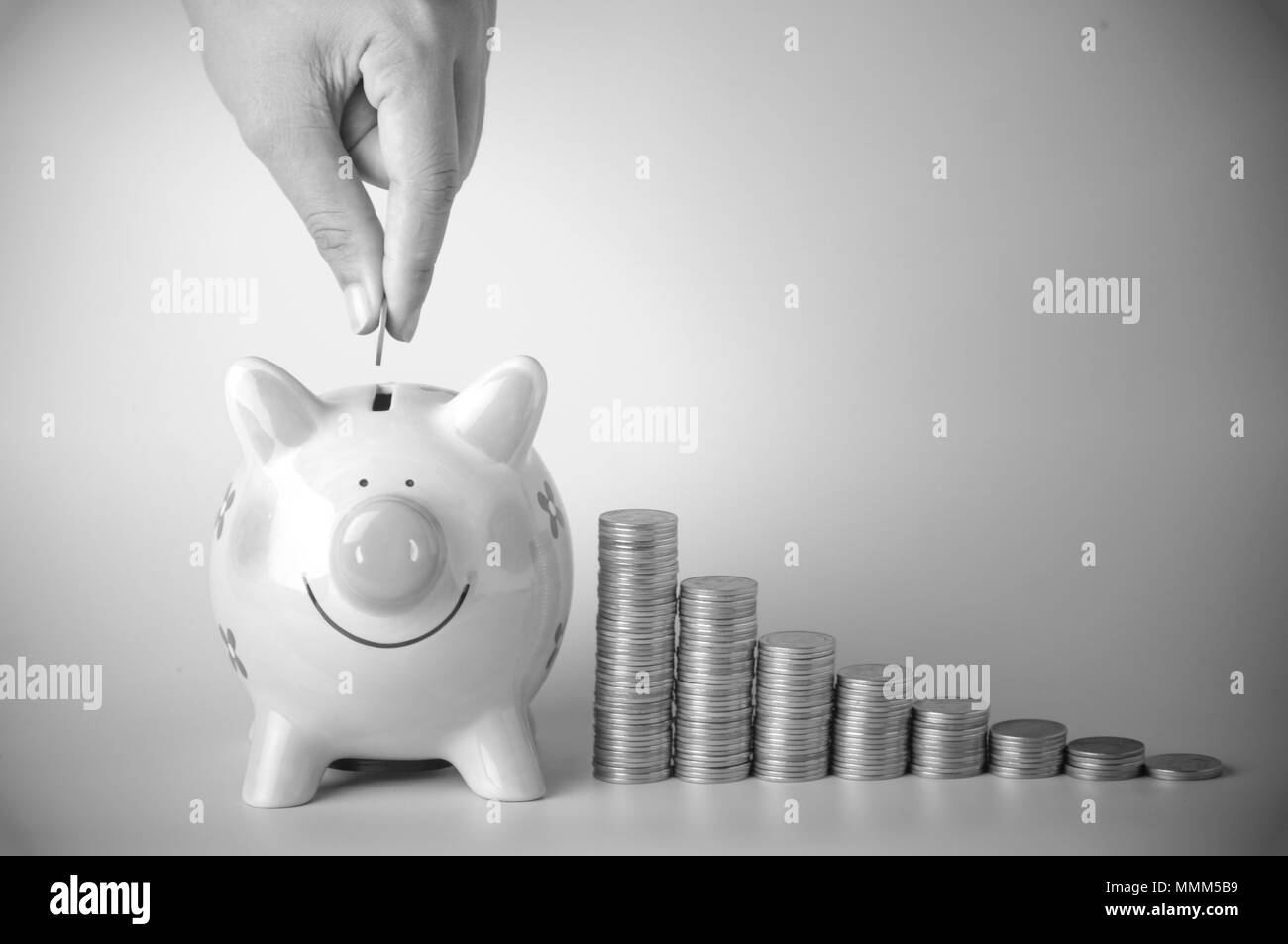 hand put money on pink of piggy bank and  pile of coins on blue background, concept in growth, save and investment in business, black and white color - Stock Image